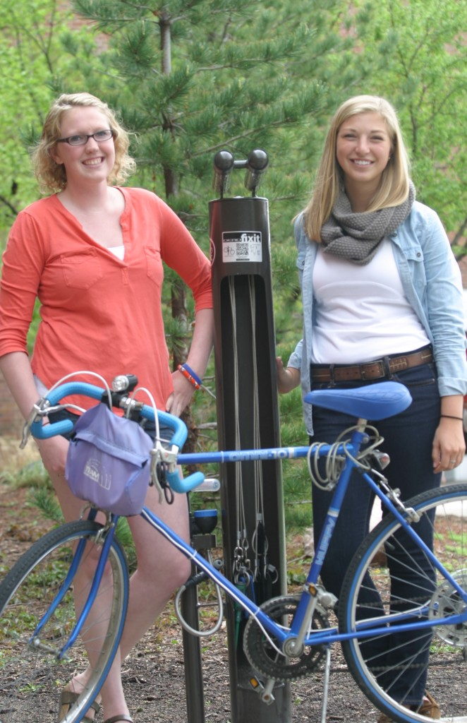 Sam Good '13 and Katie Barta '13 stand next to the new bike repair station near between Lund Center and the C. Charles Jackson Campus Center.