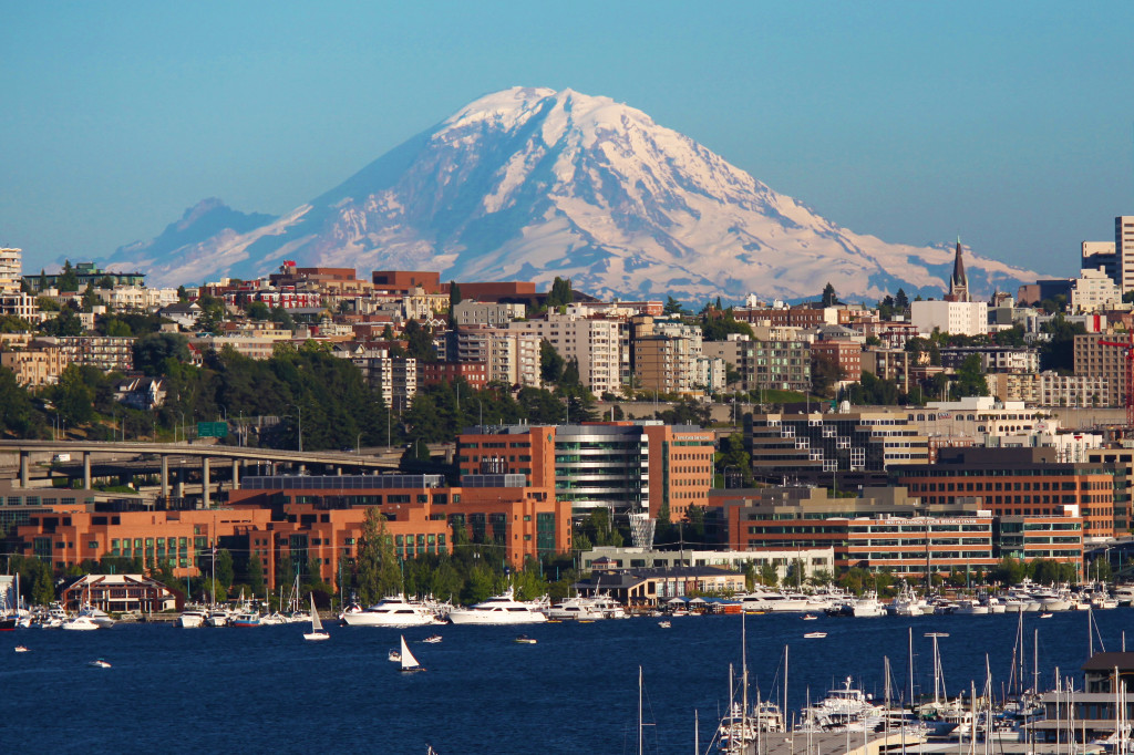 The Fred Hutchinson Cancer Research Center (red brick building) is located near downtown Seattle with Lake Union in the foreground and Mt. Rainier in the background.