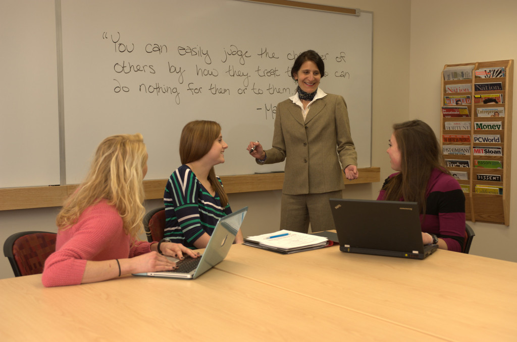 Lund Dean works with three students in a Beck Hall classroom.