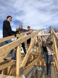 Gustavus students volunteer roofing a Habitat for Humanity home.