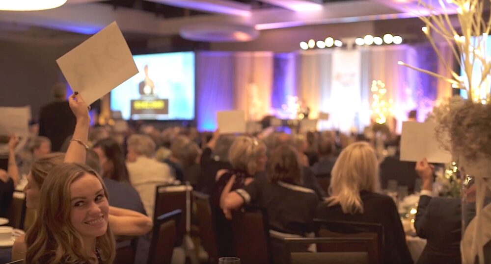 Attendees hold up bidding numbers during A Royal Affair's live auction.